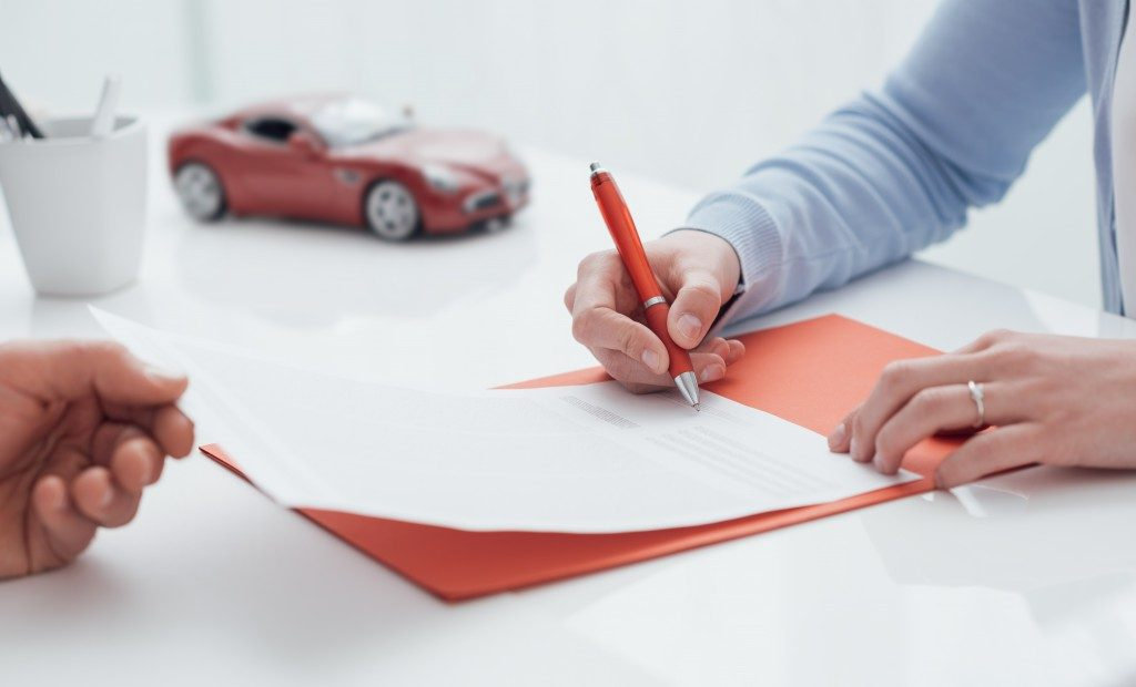 Woman signing a car insurance contract