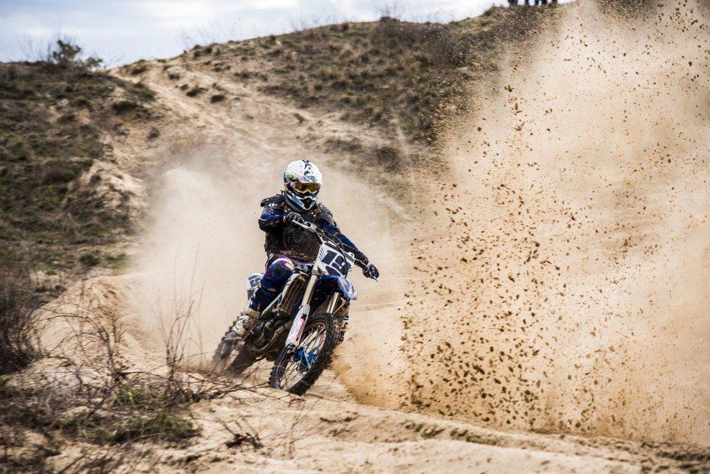 man weaving through dirt as he rides his bike