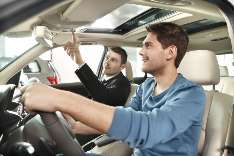 Salesman showing the car features to the buyer