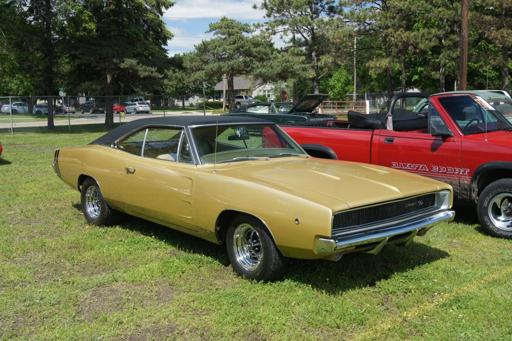 mustard dodge charger next to a red pickup