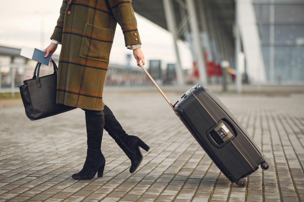 woman holding plane ticket and luggage travelling